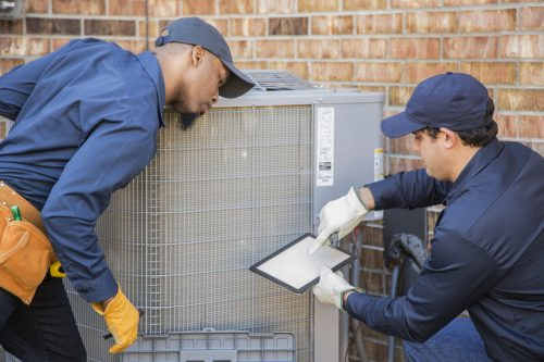 Two technicians performing repair services for an outdoor AC unit in St. Louis MO