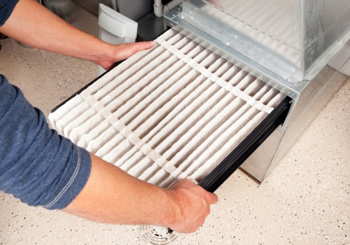 Technician replacing a filter during Furnace Service in St. Louis MO