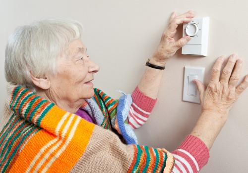 Elderly woman adjusting her thermostat after Furnace Repair in St. Louis MO